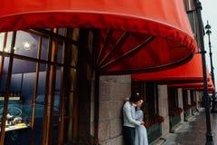Un par cariñoso abraza debajo del toldo rojo de la tienda en la calle abrace foto de archivo