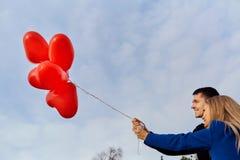 Un par cariñoso con los globos contra el cielo azul fotos de archivo