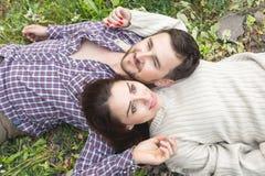 Un par cariñoso de inconformistas pone en la hierba Foto de archivo