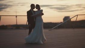 Un par cariñoso del casar abraza nuevamente en la puesta del sol almacen de video