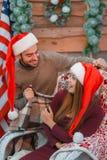 Un par cariñoso en casquillos de la Navidad Un individuo cubre a la muchacha con una manta indoor fotos de archivo libres de regalías