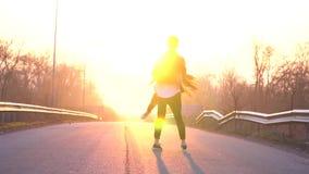 Un par cariñoso en el amanecer en el camino, un hombre está circundando a una mujer en el aire almacen de video