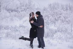 Un par cariñoso en un paseo del invierno Historia de amor de la nieve, magia del invierno Hombre y mujer en la calle escarchada E imagenes de archivo