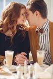 Un par cariñoso que goza de un café en el café Foto de archivo