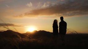 Un par cariñoso que se coloca en la puesta del sol almacen de metraje de vídeo
