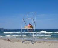 Un par cariñoso se está sentando en un aparejo del rescate de la playa durante una pequeña tormenta fotos de archivo