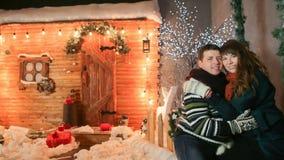 Un par cariñoso se goza contra un fondo de las decoraciones del cuento de hadas Tema de la Navidad y del Año Nuevo foto de archivo