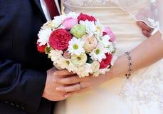 Manos de la boda con las flores Foto de archivo libre de regalías