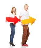 Un par de adolescentes felices que sostienen flechas coloridas Fotos de archivo libres de regalías
