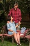 Un par de adultos jovenes se relajan en el jardín foto de archivo libre de regalías
