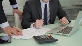 Un par de agentes compara las cartas de los tipos de cambio en el papel con los resultados en el ordenador portátil almacen de video