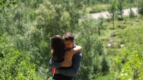 Un par de amantes se coloca contra la perspectiva de los verdes vivos del bosque honeymoon Beso en el fondo del metrajes
