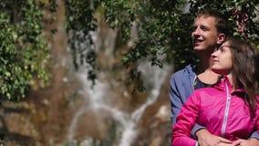 Un par de amantes se opone a una cascada honeymoon beso en el fondo de las montañas Concepto de familia Pareja almacen de video