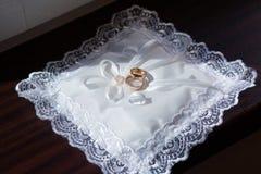 Un par de anillos de bodas en una almohada blanca fotografía de archivo