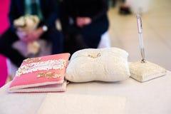 Un par de anillos de bodas en una almohada blanca imagenes de archivo