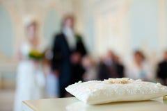 Un par de anillos de bodas en una almohada blanca imagen de archivo libre de regalías