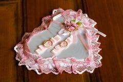 Un par de anillos de bodas en una almohada en forma de corazón imagen de archivo libre de regalías