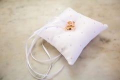Un par de anillos de bodas entrelazados con la cinta en una almohada fotos de archivo libres de regalías