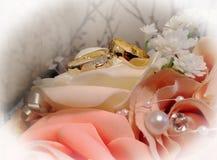 Un par de anillos de bodas que descansan sobre un ramo nupcial Fotografía de archivo