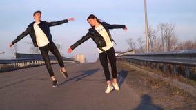 Un par de bailarines en las chaquetas de cuero y los pantalones negros baila en el camino por la mañana, cámara lenta almacen de metraje de vídeo