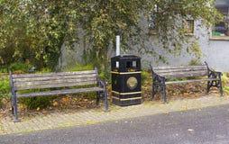 Un par de bancos de parque dilapidados y de un cubo de la basura del Ayuntamiento en el borde de la carretera en el pequeño puebl Imagen de archivo