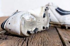 Un par de botas viejas del fútbol, zapato del fútbol del uso en un de madera viejo Fotografía de archivo