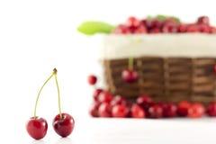Un par de cerezas con una cesta en el fondo fotografía de archivo