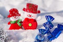 Un par de felices muñecos de nieve en la nieve con la Navidad juega con caramelos azules y un copo de nieve plateado Feliz Navida Fotografía de archivo