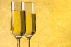 Un par de flautas del fondo abstracto de oro del champán Foto de archivo libre de regalías