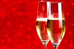 Un par de flautas del fondo abstracto rojo del champán Imagenes de archivo
