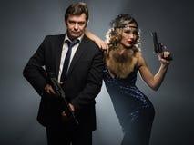 Un par de gángsteres, de un hombre y de mujer con los armas imagenes de archivo