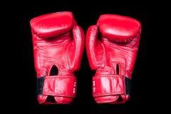 Un par de guantes de boxeo rojos viejos en un fondo negro imágenes de archivo libres de regalías