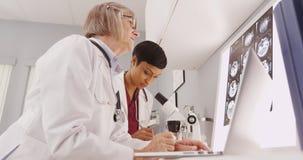 Un par de investigadores médicos que miran a través de un microscopio Imágenes de archivo libres de regalías