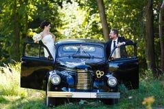 Un par de la boda con el coche viejo Foto de archivo libre de regalías