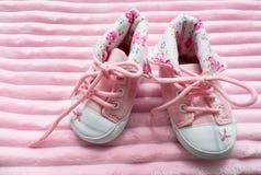 Un par de las zapatillas de deporte de los niños para las muchachas en un fondo rosado imagen de archivo libre de regalías