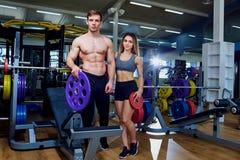 Un par de los deportes con los músculos en el cuerpo está presentando en gimnasio Fotos de archivo