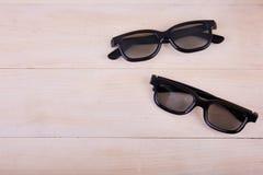 Un par de los vidrios 3D en el fondo de una tabla de madera Foto de archivo libre de regalías