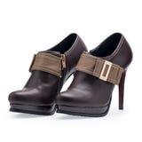Un par de los zapatos de las mujeres broncea los estiletes con la hebilla del metal Foto de archivo libre de regalías
