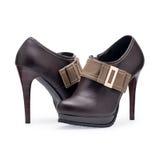 Un par de los zapatos de las mujeres broncea los estiletes con la hebilla del metal Imagen de archivo