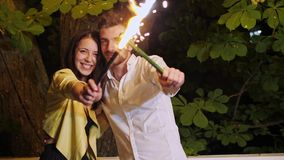 Un par de lujo en café en la noche con las bengalas del fuego artificial almacen de metraje de vídeo
