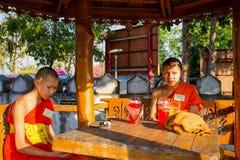 Un par de monjes jovenes se sientan y descansan fuera del templo, Tailandia Fotos de archivo libres de regalías