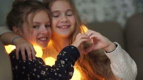 Un par de novias adolescentes hermosas juegan en casa en cama Las muchachas muestran un corazón con sus manos Amistad de la escue almacen de video