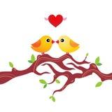 Un par de pájaros estilizados en una ramificación de árbol Imágenes de archivo libres de regalías
