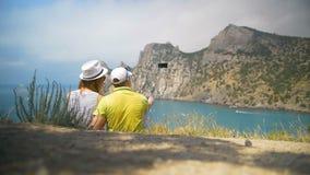 Un par de personas asentadas en la playa y la observación del mar almacen de metraje de vídeo