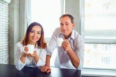 Un par de personas de mediana edad con las tazas en sus manos dentro fotos de archivo libres de regalías