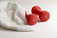 Un par de pesas de gimnasia y de toalla del sudor Foto de archivo libre de regalías