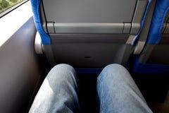 Un par de piernas vestidas en viajes de los vaqueros por el tren foto de archivo