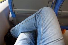 Un par de piernas vestidas en viajes de los vaqueros por el tren imagen de archivo
