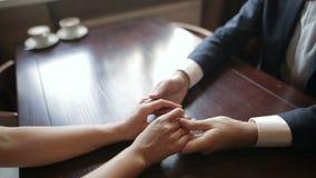 Un par de recienes casados que llevan a cabo las manos en un café Ciérrese para arriba de manos humanas almacen de metraje de vídeo