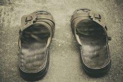 Un par de sandalias marrones colocadas en un piso del cemento foto de archivo